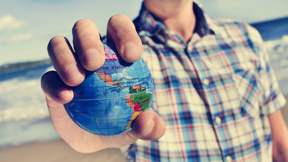мужчина держит в руках макет земного шара