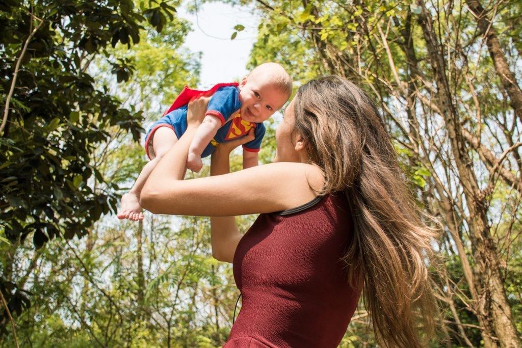 Мама держит младенца в костюме супергероя